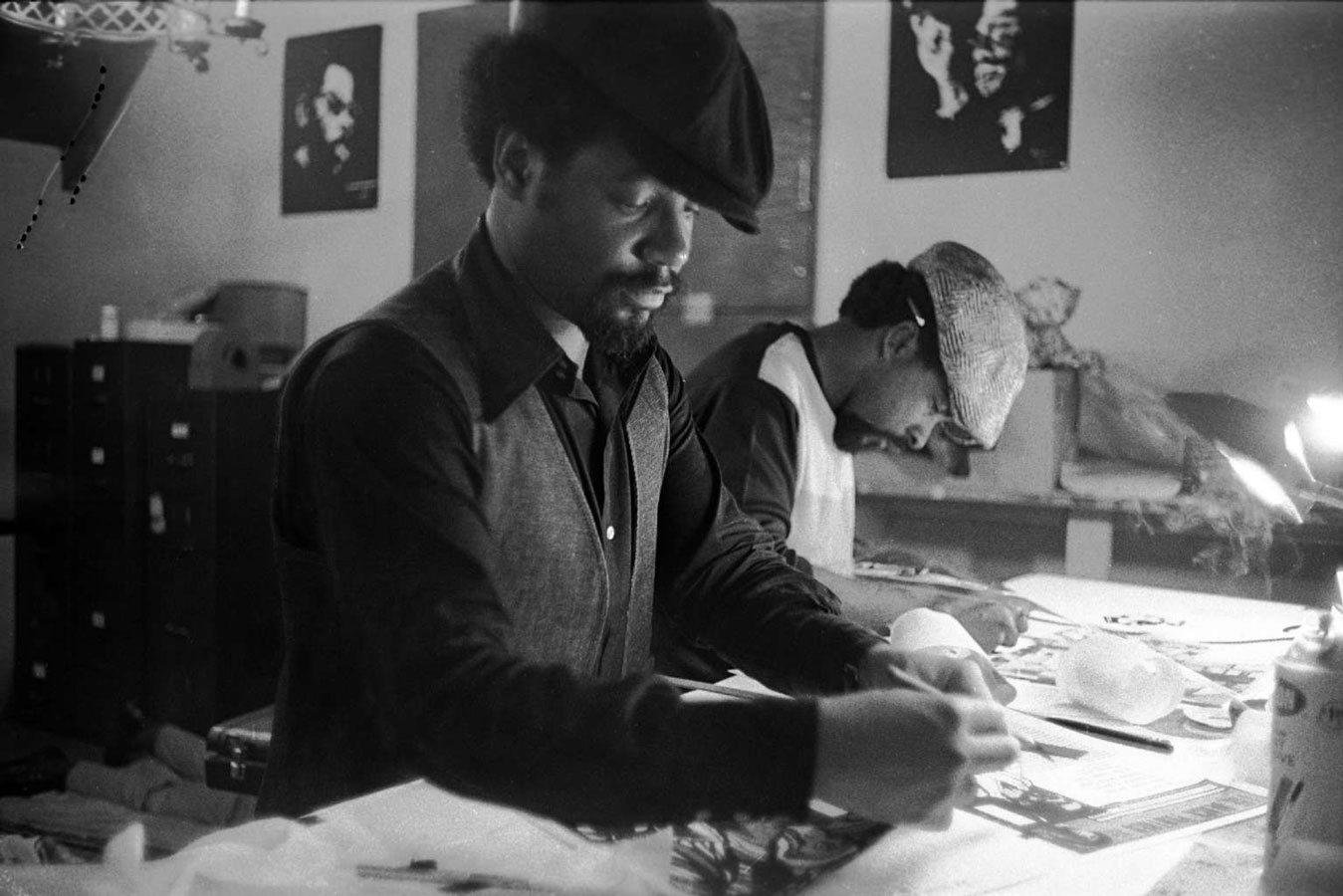 Emory Douglas helps lay out The Black Panther, John Seale to his left.
